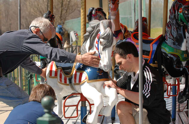 Dave Hoffman, left, steadies a merry-go-round horse as Glenn Kewley, center, and Eric Brazee, right, secure the horse?s mounting points during opening day at Hoffman?s Playland in Loudonville, Friday lunchtime, April 2, 2010. Hoffman's will remain open all next week for spring break. (Will Waldron / Times Union) Photo: Times Union