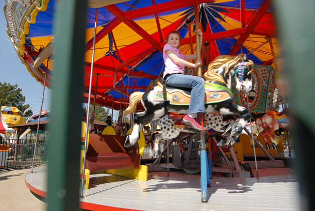 Catherine Loupessis, age 8, takes a spin on the merry-go-round during opening day at Hoffman?s Playland in Loudonville, Friday lunchtime April 2, 2010. Hoffman's will remain open all next week for spring break. (Will Waldron / Times Union) Photo: Times Union