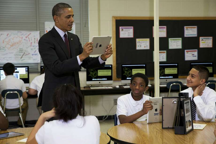 President Barack Obama records students on a classroom iPad while visiting a seventh grade classroom before speaking about goals of connecting students to next generation broadband and wireless technology within five years, Tuesday, Feb. 4, 2014, at Buck Lodge Middle School in Adelphi, Md. (AP Photo/Jacquelyn Martin) Photo: Jacquelyn Martin, Associated Press