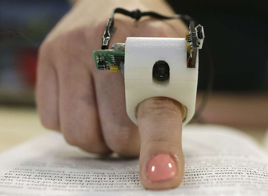 In this Thursday, June 26, 2014 photo, a model wears a FingerReader ring at the Massachusetts Institute of Technology's Media Lab in Cambridge, Mass. Researchers designed and developed the instrument, which enables people with visual disabilities to read text printed on paper or electronic devices. (AP Photo/Stephan Savoia) Photo: Stephan Savoia, Associated Press