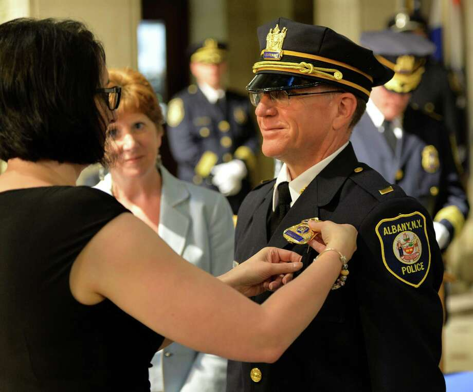 Newly promoted Albany police Lt. Thomas Gibbons has his new Lieutenant's shield pinned to his uniform Tuesday morning July 8, 2014, by his wife Patti during a promotion and swearing-in ceremony held at City Hall in Albany, N.Y. Fourteen new recruits were sworn-in as well during the ceremony. (Skip Dickstein / Times Union) Photo: SKIP DICKSTEIN / 00027689A