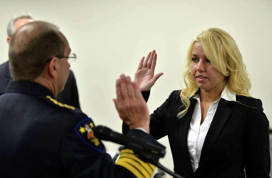 Kayla Messier is sworn-in by Troy police chief John Tedesco, left, as two new police recruits join the Troy force Tuesday morning, July 8, 2014, in Troy, N.Y. (Skip Dickstein / Times Union) Photo: SKIP DICKSTEIN / 00027690A