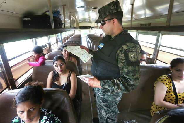 Captain Carlos Madrid of the Honduras Military Police checks the identification papers of a Honduran woman traveling with her two children to Guatemala, near the border town of Corinto, Honduras. One child was born in Honduras and the other was born in Guatemala, and they were allowed to pass. Friday, June 27, 2014. Photo: Bob Owen, San Antonio Express-News / ©2013 San Antonio Express-News
