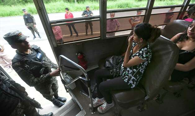 A bus traveling from Honduras to Guatemala is detained as Honduran Military Police check identification papers of the travelers, near Corinto, Honduras at the Guatemala border. The men were searched off the bus while the women had their ID's checked inside. Friday,