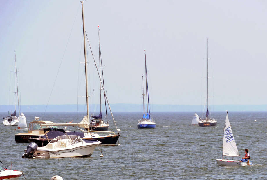 A small sailboat makes its way through other boats moored in Greenwich Harbor, off the coast of Greenwich, Conn., Wednesday, July 2, 2014. Photo: Bob Luckey / Greenwich Time