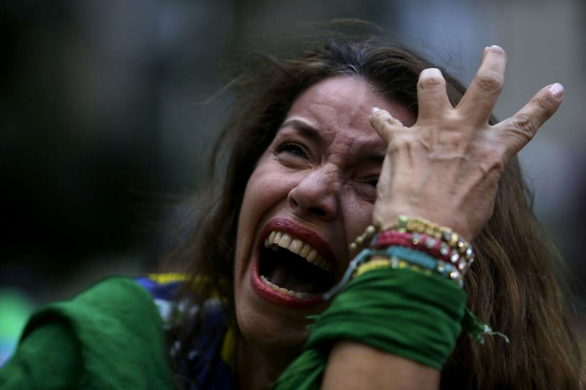 A Brazilian soccer fan cries as she watches her team get beat during a live telecast of the semifinals World Cup soccer match between Brazil and Germany, in Belo Horizonte, Brazil, Tuesday, July 08, 2014. (AP Photo/Bruno Magalhaes)