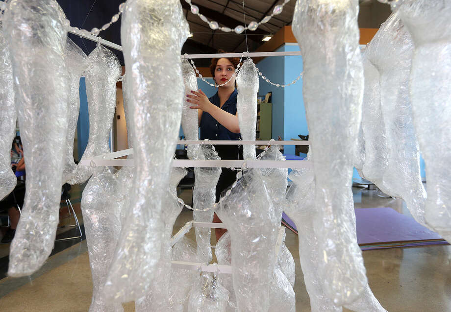 """Mattie Myers, 15, a junior at Henry Ford Academy, surveys her art project for SAY Sí's annual exhibit about taboos, titled """"Stories Seldom Told."""" Her reproductions of legs, called """"Every BODY is Beautiful,"""" seeks to inspire pride in viewers' bodies. Photo: Photos By Jerry Lara / San Antonio Express-News / © 2014 San Antonio Express-News"""