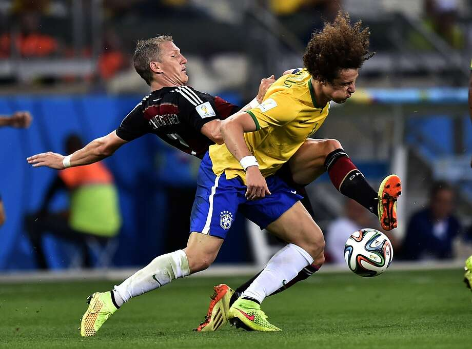 Brazil's David Luiz, right, battles for the ball with Germany's Bastian Schweinsteiger during the World Cup semifinal soccer match between Brazil and Germany at the Mineirao Stadium in Belo Horizonte, Brazil, Tuesday, July 8, 2014.  Photo: Martin Meissner, Associated Press