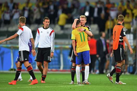 BELO HORIZONTE, BRAZIL - JULY 08:  Andre Schuerrle of Germany consoles Oscar of Brazil after Germany's 7-1 win during the 2014 FIFA World Cup Brazil Semi Final match between Brazil and Germany at Estadio Mineirao on July 8, 2014 in Belo Horizonte, Brazil. Photo: Laurence Griffiths, Getty Images / 2014 Getty Images