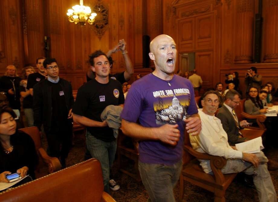 SEIU members including Carey Dall and their supporters marched through the Board of Supervisors meeting before it started Tuesday July 8, 2014. Members of the SEIU protested at the San Francisco Board of Supervisors meeting over the amount paid nonprofit service agencies in the city. Photo: Brant Ward, San Francisco Chronicle