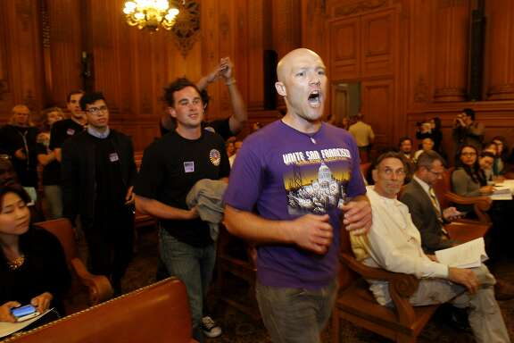 SEIU members including Carey Dall and their supporters marched through the Board of Supervisors meeting before it started Tuesday July 8, 2014. Members of the SEIU protested at the San Francisco Board of Supervisors meeting over the amount paid nonprofit service agencies in the city.