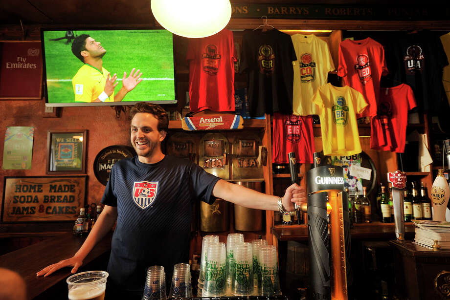 Bartender Armen Karaptian takes drink orders while his customers watch the Germany versus Brazil semifinal World Cup soccer match at Tigin Irish Pub in Stamford, Conn., on Tuesday, July 8, 2014. Germany won the match, 7-1, and will face the winner of Wednesday's Netherlands versus Argentina match. Photo: Jason Rearick / Stamford Advocate