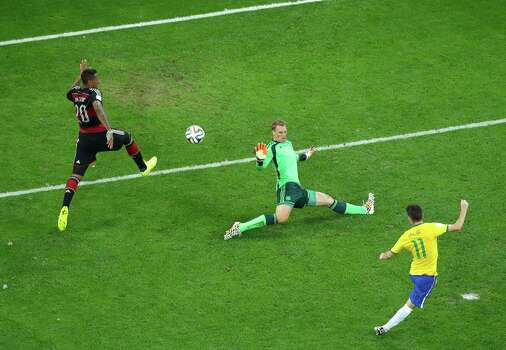 BELO HORIZONTE, BRAZIL - JULY 08:  Oscar of Brazil scores his team's first goal past Jerome Boateng and goalkeeper Manuel Neuer of Germany during the 2014 FIFA World Cup Brazil Semi Final match between Brazil and Germany at Estadio Mineirao on July 8, 2014 in Belo Horizonte, Brazil. Photo: Pool, Getty Images / 2014 Getty Images