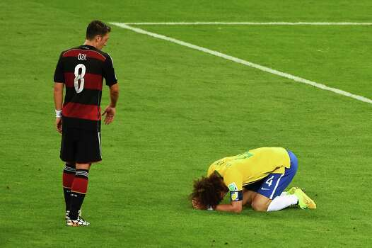 BELO HORIZONTE, BRAZIL - JULY 08:  David Luiz of Brazil reacts after being defeated 7-1 by Germany as Mesut Oezil of Germany looks on during the 2014 FIFA World Cup Brazil Semi Final match between Brazil and Germany at Estadio Mineirao on July 8, 2014 in Belo Horizonte, Brazil. Photo: Jamie McDonald, Getty Images / 2014 Getty Images