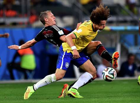 Brazil's David Luiz, right, battles for the ball with Germany's Bastian Schweinsteiger during the World Cup semifinal soccer match between Brazil and Germany at the Mineirao Stadium in Belo Horizonte, Brazil, Tuesday, July 8, 2014. (AP Photo/Martin Meissner) Photo: Martin Meissner, Associated Press / AP