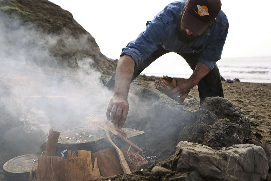Tom Accettola, research and development director at Juniper Ridge, builds a redwood bonfire as part of a smoke distillation technique used to extract fragrance. Photo: Andre Zandona, The Chronicle