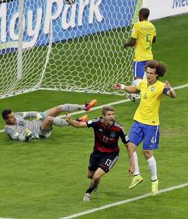 Germany's Thomas Mueller celebrates after scoring his teams first goal during the World Cup semifinal soccer match between Brazil and Germany at the Mineirao Stadium in Belo Horizonte, Brazil, Tuesday, July 8, 2014. (AP Photo/Hassan Ammar)