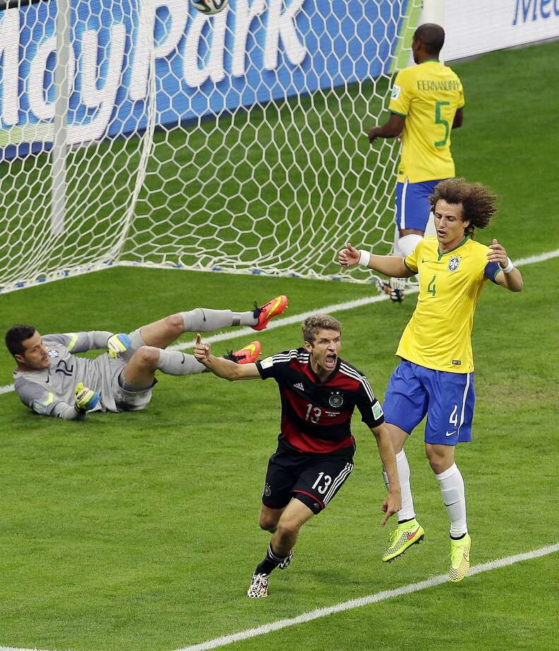 Thomas Mueller (13) celebrates in front of Brazil's David Luiz (4) after scoring first in Germany's record-breaking victory. Photo: Hassan Ammar, Associated Press