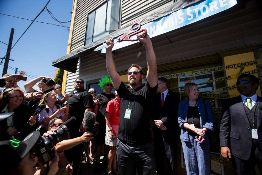 Store owner James Lathrop holds up a pair of giant scissors before cutting the police tape ribbon on the doors of Cannabis City  on Tuesday, July 8, 2014. Photo: JOSHUA BESSEX, SEATTLEPI.COM