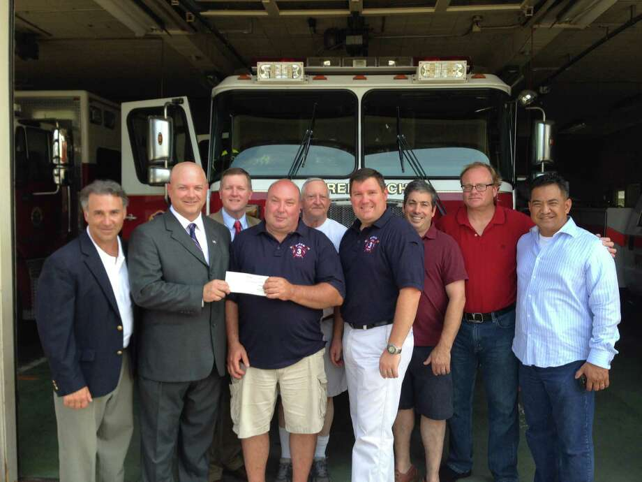 Byram Neighborhood Association Chairman, and candidate for state representative, Michael Bocchino, flanked by state Reps. Fred Camillo, left, and Stephen Walko, hands a $3,000 check to Byram Volunteer Fire Department Chief Aaron Stahl and several Byram volunteers. Photo: Justin Pottle / Greenwich Time