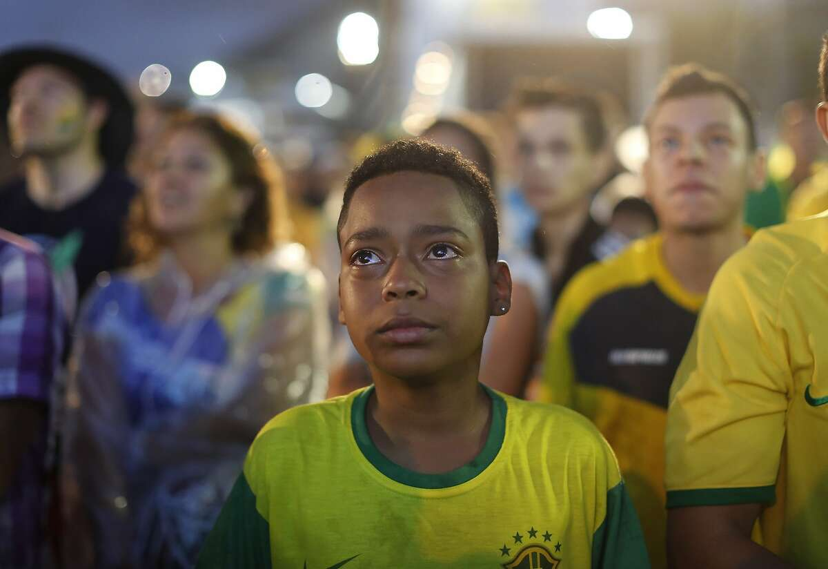 A Brazil soccer fan cries as he watches his team during a live telecast of the semi-finals World Cup soccer match between Brazil and Germany, inside the FIFA Fan Fest area on Copacabana beach.