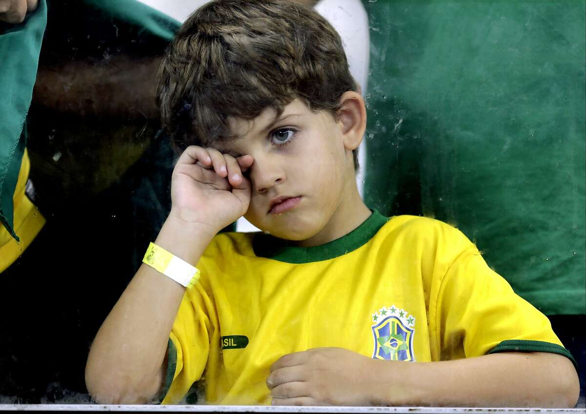 A young supporter watches players on the field after Germany defeated Brazil 7-1.