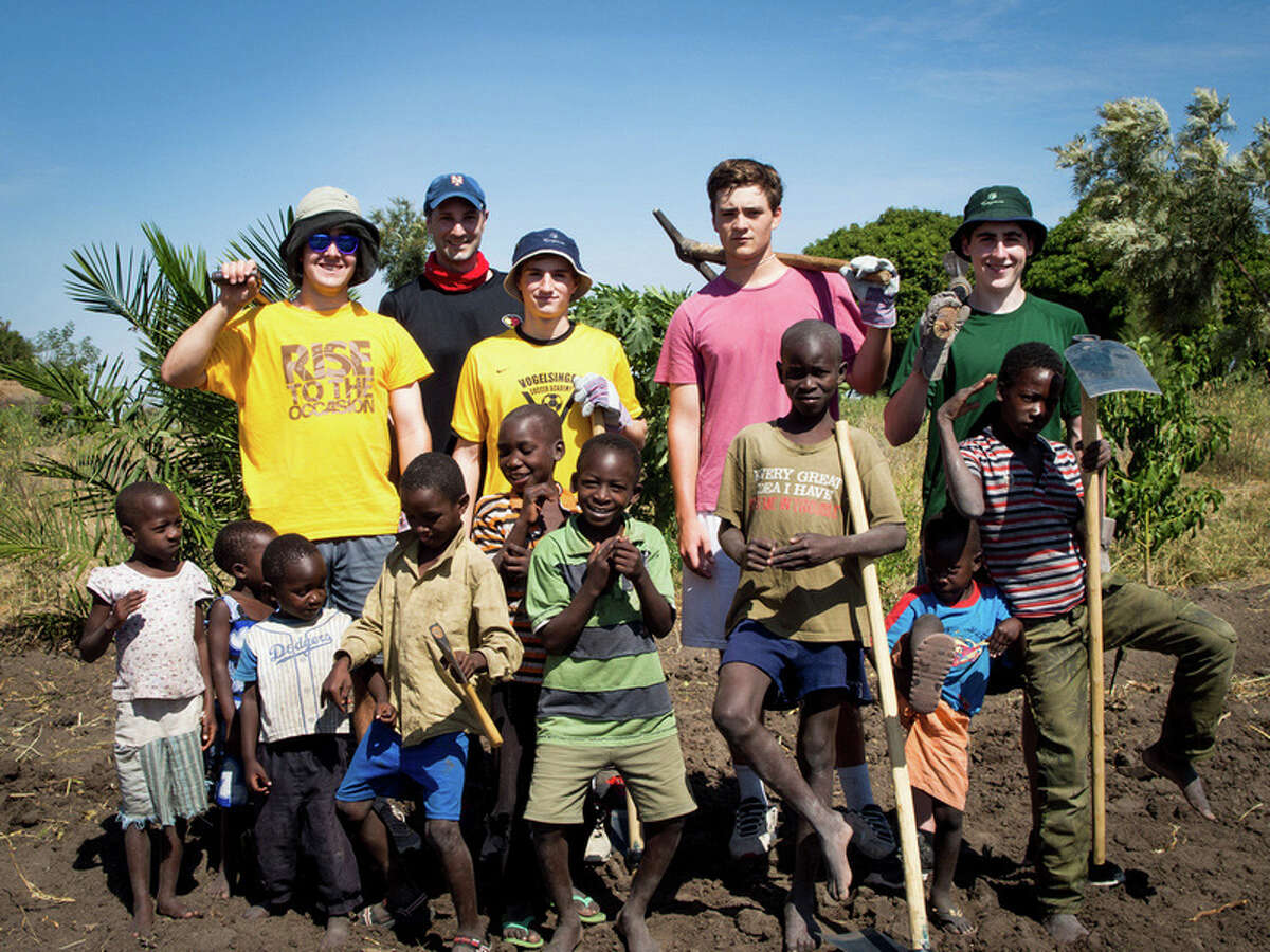 Brunswick School students (second row, left to right) Jamie MacFarlane of Greenwich, Dayton Kingery of Greenwich, Ryan Hanrahan of Bronxville, N.Y., and Jack Muccia of Rye, take a break from work in a Tanzanian farm field with native children and (rear) Brunswick environmental science teacher Dan Dychkowski. In June, the group traveled to the East African country to work at an orphanage for girls.