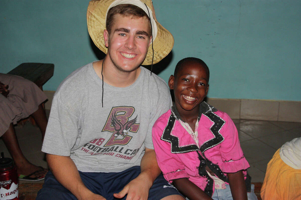 Brunswick School student Jamie MacFarlane of Greenwich shares a smile with a Tanzanian orphan girl. MacFarlane was one of four Brunswick students who traveled to the East African country in June to volunteer at an orphanage for more than 40 girls, ages 8 to 15.