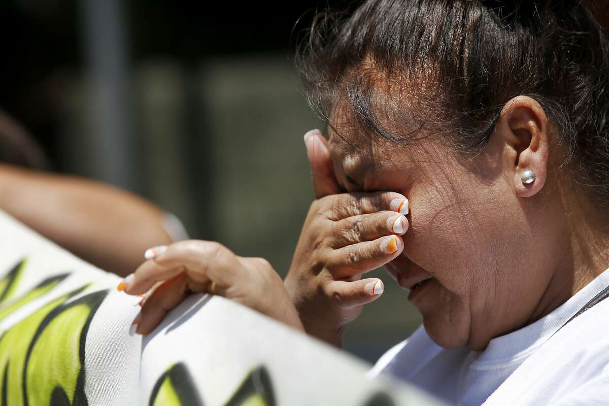 Lurdes Olvera, the godmother of Andy Lopez, sheds tears while holding a sign during a protest July 8, 2014 outside of the Sonoma County Hall of Justice in Santa Rosa, Calif. People gathered to protest D.A. Jill Ravitch to let her know that they are unhappy with the lack of charges in the case involving the death of Andy Lopez last year.
