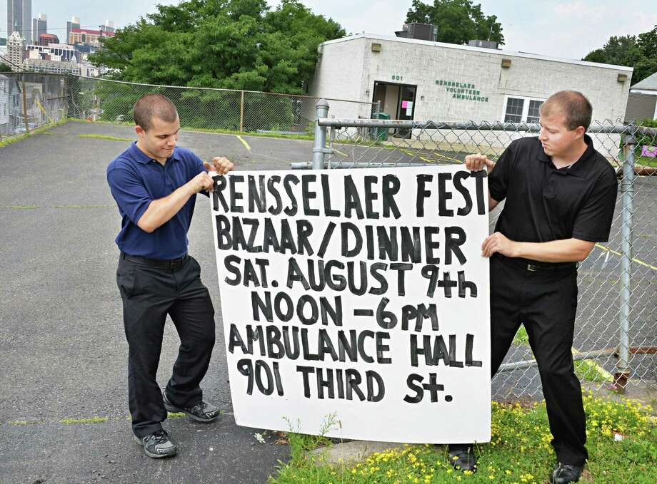 Rensselaer Fest chairman Ricky Mollenkopf, left, and co-chairman David Ellis put up a sign for a fund raiser for Rensselaer Fest at the Rensselaer Volunteer Ambulance headquarters Tuesday, July 8, 2014, in Rensselaer, N.Y.  (John Carl D'Annibale / Times Union) Photo: John Carl D'Annibale