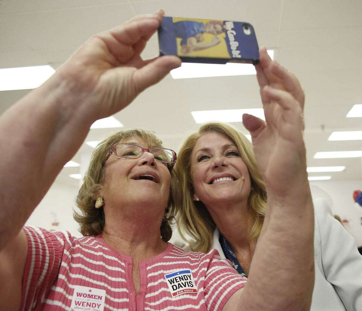 Doris Gluck, left, takes a selfie with gubernatorial candidate Wendy Davis at the La Gran Plaza campaign office in Fort Worth on Tuesday.