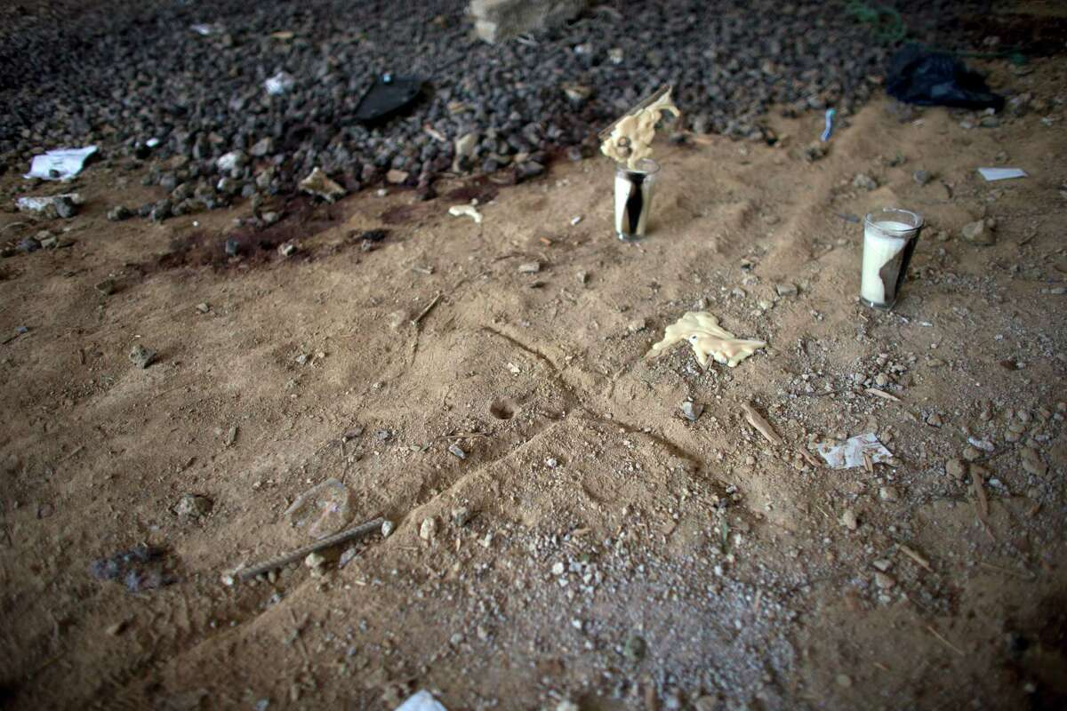 In this Thursday, July 3, 2014 photo, a cross and candles left by relatives of the dead mark the ground near bloodstains in an unfinished warehouse that was the site of a shootout between Mexican soldiers and alleged criminals on the outskirts of the village of San Pedro Limon, in Mexico state, Mexico. Mexico's Defense Department says soldiers were patrolling in one of the most violent, lawless corners of the country on June 30 when they came under fire from a warehouse where a gang of 21 men and one woman were hiding. Mexico's military says one soldier was wounded, and all 22 suspects were killed. (AP Photo/Rebecca Blackwell)