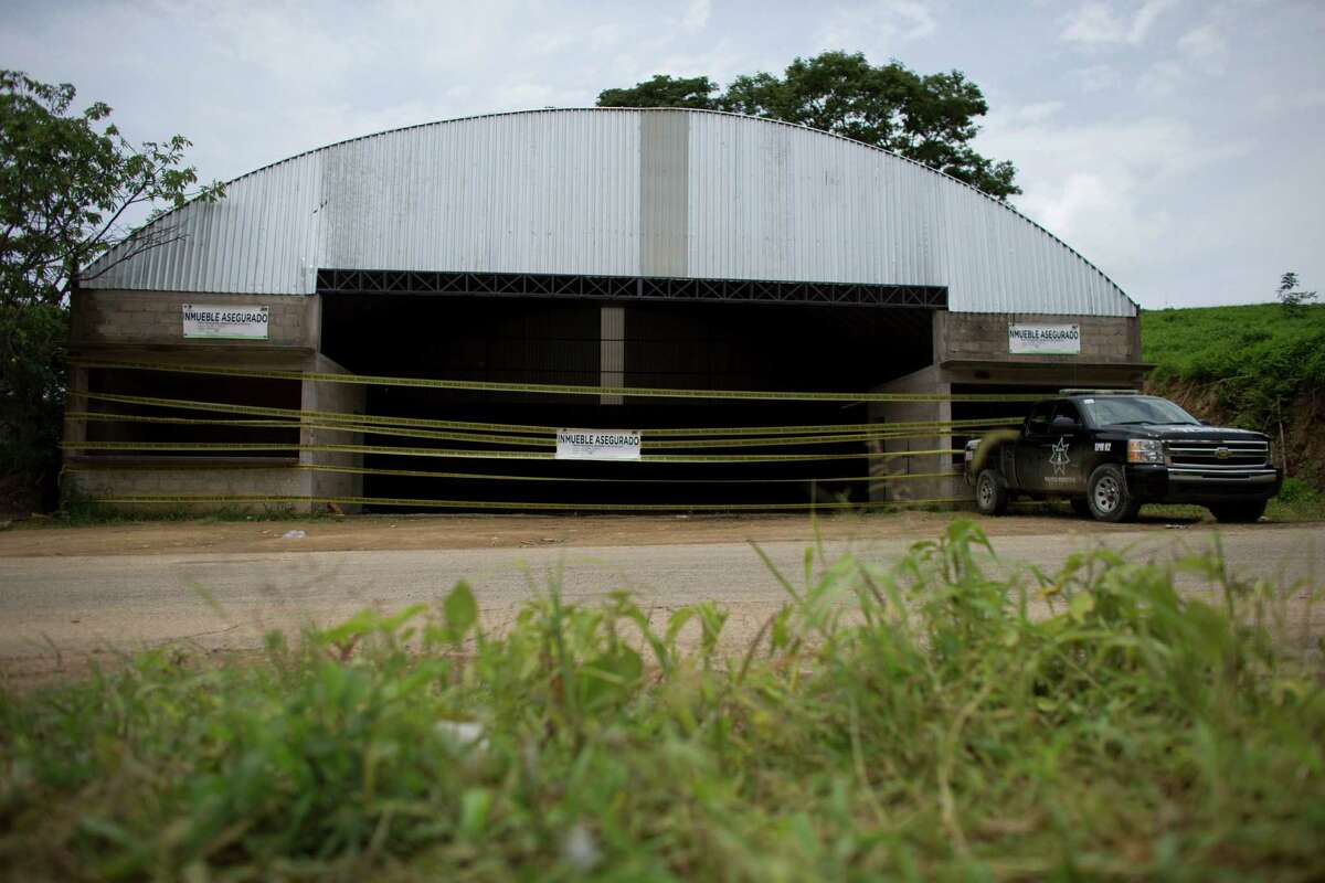 In this Thursday, July 3, 2014 photo, a state police vehicle sits parked outside a warehouse that was the site of one of a shootout between Mexican soldiers and alleged criminals on the outskirts of the village of San Pedro Limon, in Mexico state, Mexico. Despite that heavy gunfire, only about six incoming rounds appeared to have hit the facade of the warehouse, the only part of the building with a window or door where soldiers likely would have been firing at people holed up inside. Mexico's military says one soldier was wounded, and all 22 suspects were killed. (AP Photo/Rebecca Blackwell)