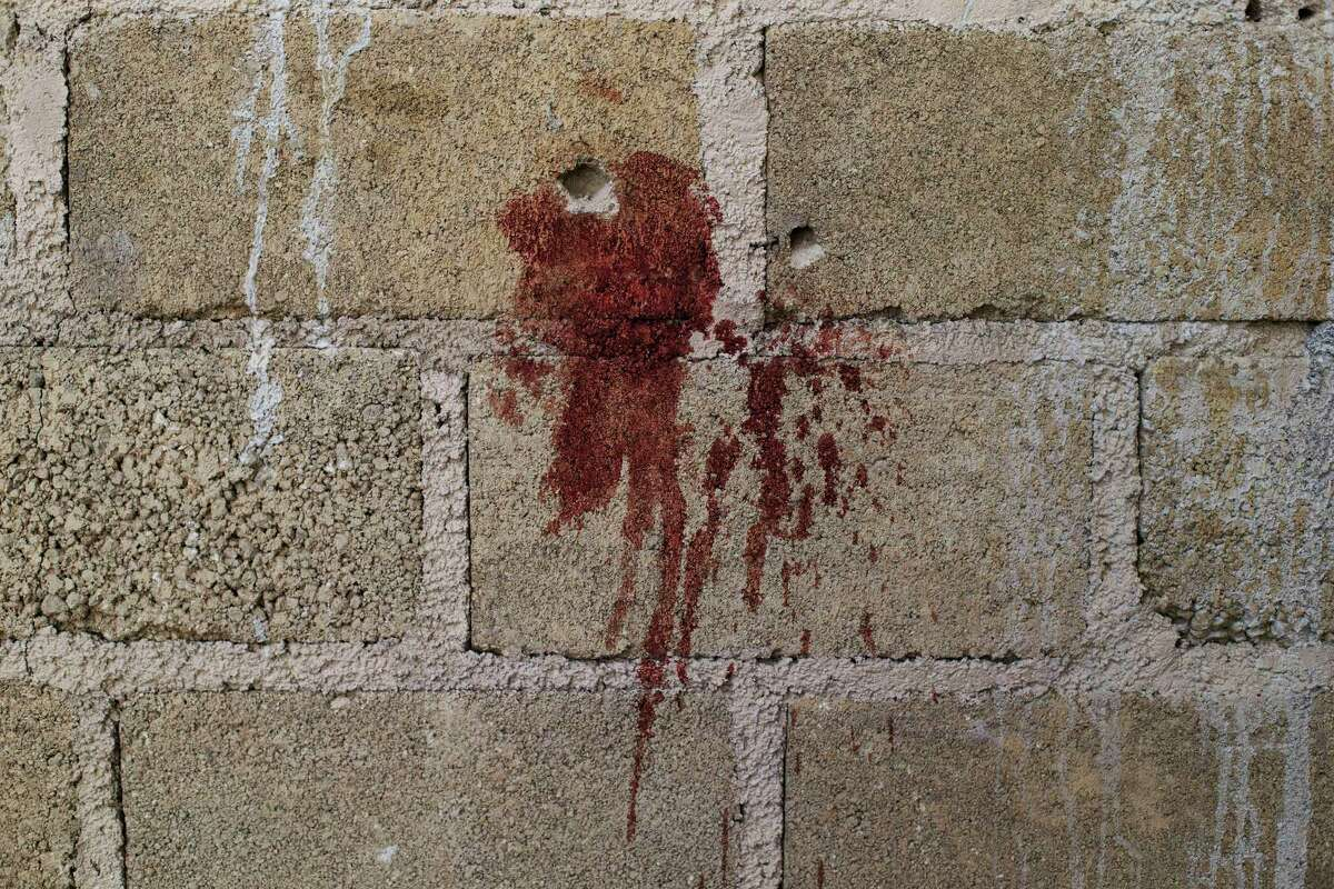 In this Thursday, July 3, 2014 photo, bullet holes and blood stain a wall above papers marking where bodies were found in an unfinished warehouse that was the site of a shootout between Mexican soldiers and alleged criminals on the outskirts of the village of San Pedro Limon in Mexico state, Mexico. The distance at which the fatal shots were fired has not made public by the Mexico State prosecutor's office, which is carrying out the autopsies. Mexico's military says one soldier was wounded, and all 22 suspects were killed. (AP Photo/Rebecca Blackwell)