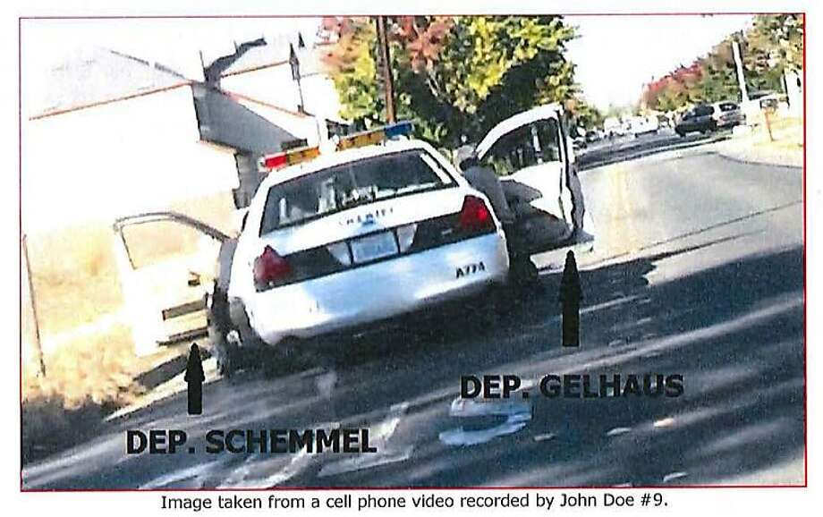 An image from a cell phone video taken by a witness, and released by the Sonoma County District Attorney's Office, shows Sonoma County Sheriff's Deputies Michael Schemmel (left) and Erick Gelhaus (right) crouching behind the doors of their patrol vehicle after Gelhaus fatally shot 13-year-old Andy Lopez on Oct. 22, 2013. Gelhaus said he mistook the boy's replica AK-47 pellet gun for a real rifle. Photo: Courtesy Sonoma County District