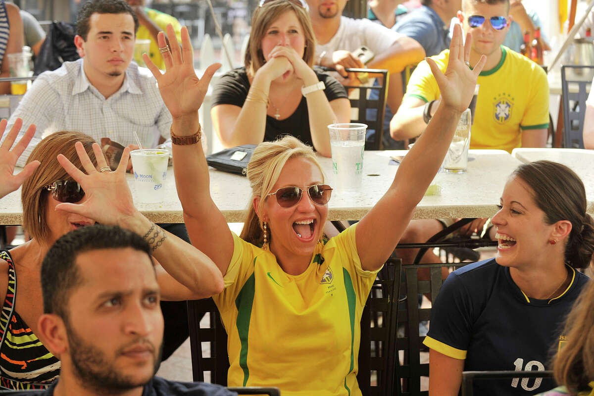 Carolina Daluz, center, cheers on Brazil while watching the Germany versus Brazil semifinal World Cup soccer match at Tigin Irish Pub in Stamford, Conn., on Tuesday, July 8, 2014. Germany won the match, 7-1, and will face the winner of Wednesday's Netherlands versus Argentina match.