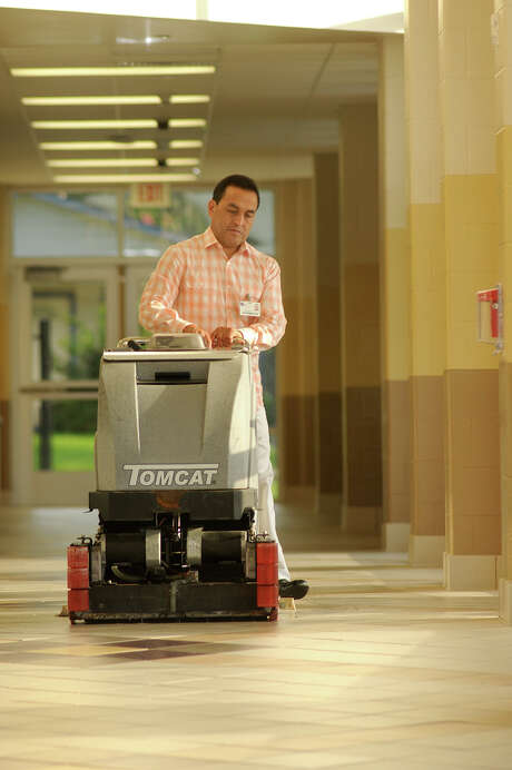 Custodian Jose Grimaldo, recently honored for his 16th year with Conroe ISD, works on the main hallway floor at Washington Junior High. Photo: Jerry Baker, Freelance