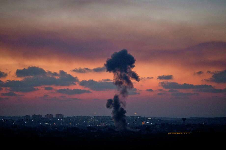 Smoke rises following an Israeli strike on Gaza, as seen from the Israel-Gaza Border, Tuesday, July 8, 2014. The Israeli military launched a major offensive in the Hamas-ruled Gaza Strip on Tuesday, striking more than 100 sites and mobilizing troops for a possible ground invasion in what Israel says is an operation aimed at stopping a heavy barrage of rocket attacks from the Palestinian territory.(AP Photo/Ariel Schalit) ORG XMIT: ASC115 Photo: Ariel Schalit / AP