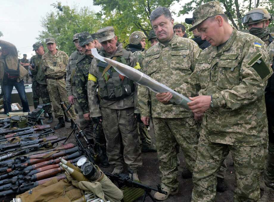 Ukrainian President Petro Poroshenko (second from right) and Defense Minister Valery Heletey examine weapons and ammunition during a visit to army headquarters near Izyum. Photo: Genya Savilov / Getty Images / AFP
