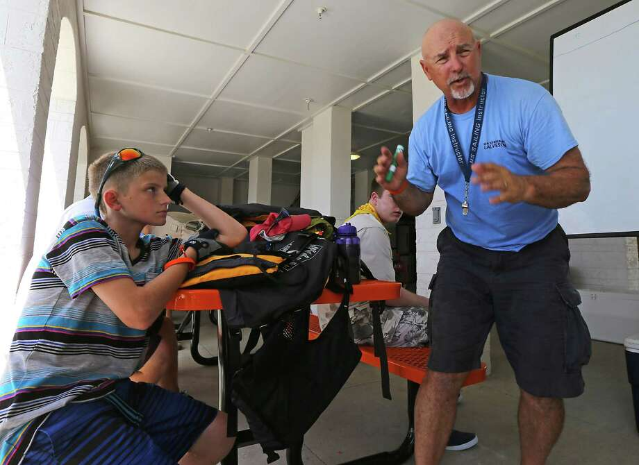 Galveston Community Youth Sailing Center, Director Mike Janota right, discusses sailing instructions as Zack Creason left, with Boy Scout troop 285 from Little Elm, Texas looks on during the Galveston Nautical Adventures program at Sea Scout Base Galveston Tuesday, July 8, 2014, in Galveston. Photo: James Nielsen, Houston Chronicle / © 2014  Houston Chronicle