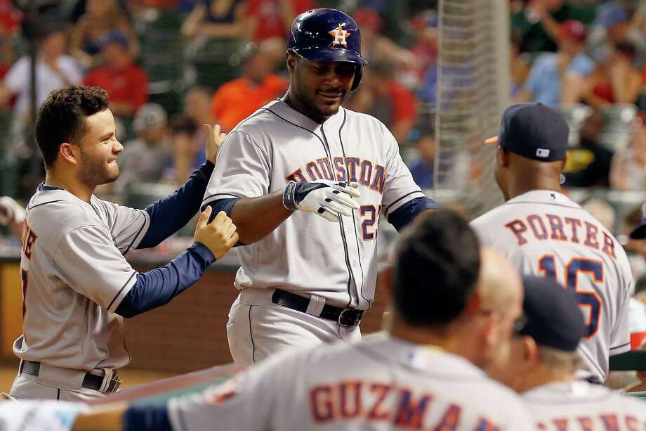 Jose Altuve, left, leads off the welcoming committee for Chris Carter, center, after the designated hitter's second home run Tuesday night - a solo shot in the eighth inning. Photo: Tom Pennington, Staff / 2014 Getty Images