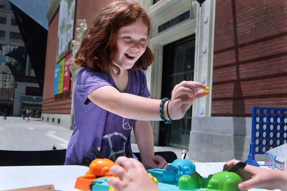Amelia Naperala, 9, of San Francisco shows brother Kyle the gold marble in Hungry Hungry Hippos during a lunchtime board games event at Jessie Square Plaza at the Contemporary Jewish Museum in San Francisco, Calif. on Tuesday, July 8, 2014. The event will take place on Tuesdays July 15, 22, 29 and August 12, 19 and 26 from noon to 1 p.m. Photo: Kevin N. Hume, The Chronicle
