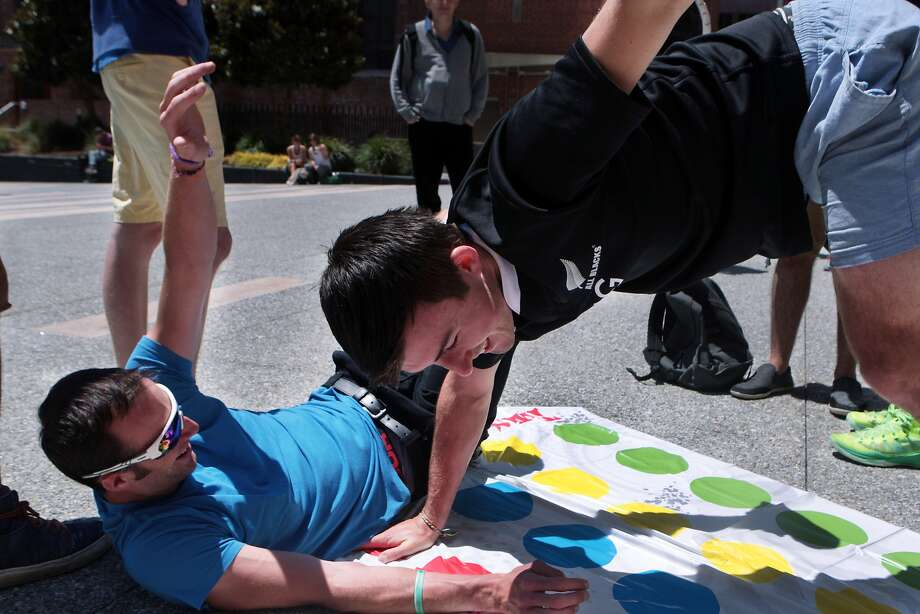 Owen Davies, left, of Auckland, New Zealand falls over while Brendan King of Wellington, New Zealand keeps his balance while playing Twister during a lunchtime board games event at Jessie Square Plaza at the Contemporary Jewish Museum in San Francisco, Calif. on Tuesday, July 8, 2014. The event will take place on Tuesdays July 15, 22, 29 and August 12, 19 and 26 from noon to 1 p.m. Photo: Kevin N. Hume, The Chronicle