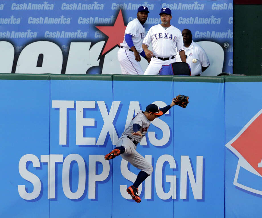 Astros center fielder George Springer tries to make the writing on the wall come true, but he is unable to reach a triple by the Rangers' Adrian Beltre in the fourth inning Tuesday night. Photo: Tony Gutierrez, STF / AP