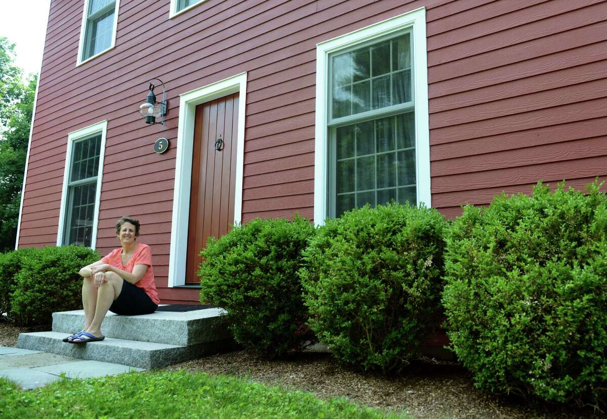 Stacy Prince sits outside her energy efficient home in Westport, Conn., Tuesday, July 8, 2014.