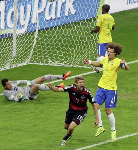 Germany's Thomas Mueller celebrates after scoring his team's first goal in what turned out to be a rout of Brazil on Tuesday. Mueller's five goals in the tournament trail only Colombia's James Rodriguez, who netted six. Photo: Hassan Ammar, Associated Press / AP