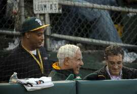 A's owner Lew Wolff, center, smiles in the third inning as the A's scored multiple times as the Oakland Athletics played the San Francisco Giants on Tuesday, July 8, 2014, at O.co Coliseum in Oakland, Calif.
