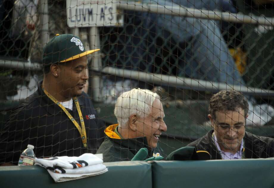 Many Oakland fans are unhappy with co-owner Lew Wolff (center) even as they enjoy this year's accomplishments by his team. Photo: Carlos Avila Gonzalez, The Chronicle
