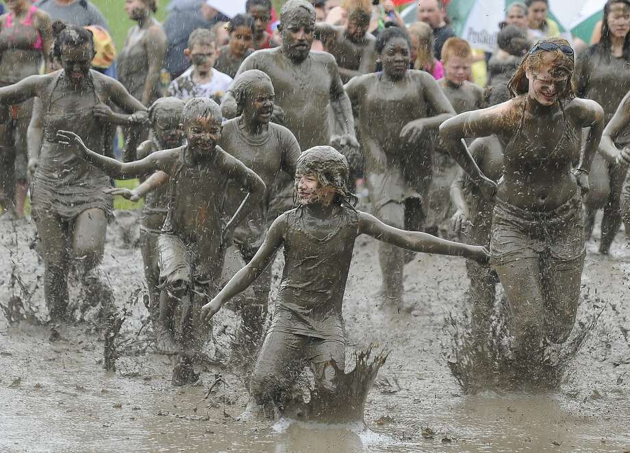 Runners race through mud at the Annual Wayne county Parks Mud Day at Hines Park- Nankin Mills Area in Westland, Mich., on Tuesday, July 8, 2014. (AP Photo/Detroit News, Daniel Mears) Photo: Daniel Mears, Associated Press
