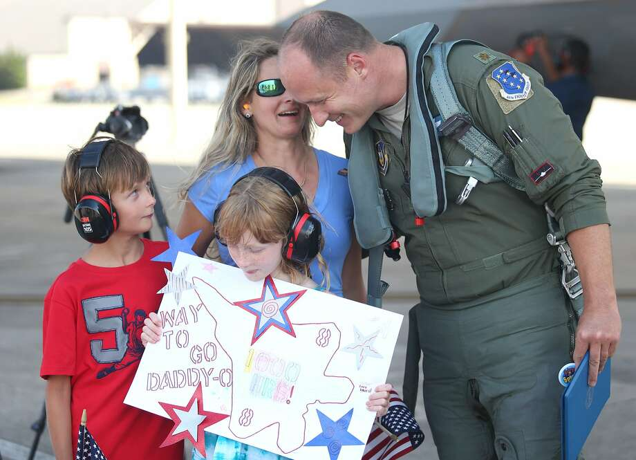 "F-22 pilot Maj. Daniel ""Magic"" Lee, right, greets his family Benton, left, Catherine, front center, and Rebecca after completing a flight, Tuesday, July 8, 2014, at Tyndall Air Force Base, Fla. Lee has logged 1,000 flight hours in F-22s. (AP Photo/The News Herald, Patti Blake) Photo: Patti Blake, Associated Press"